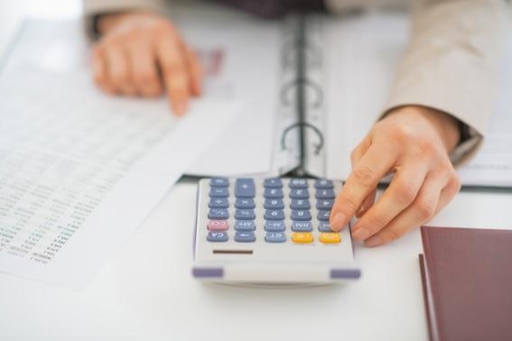 Closeup on business woman using calculator